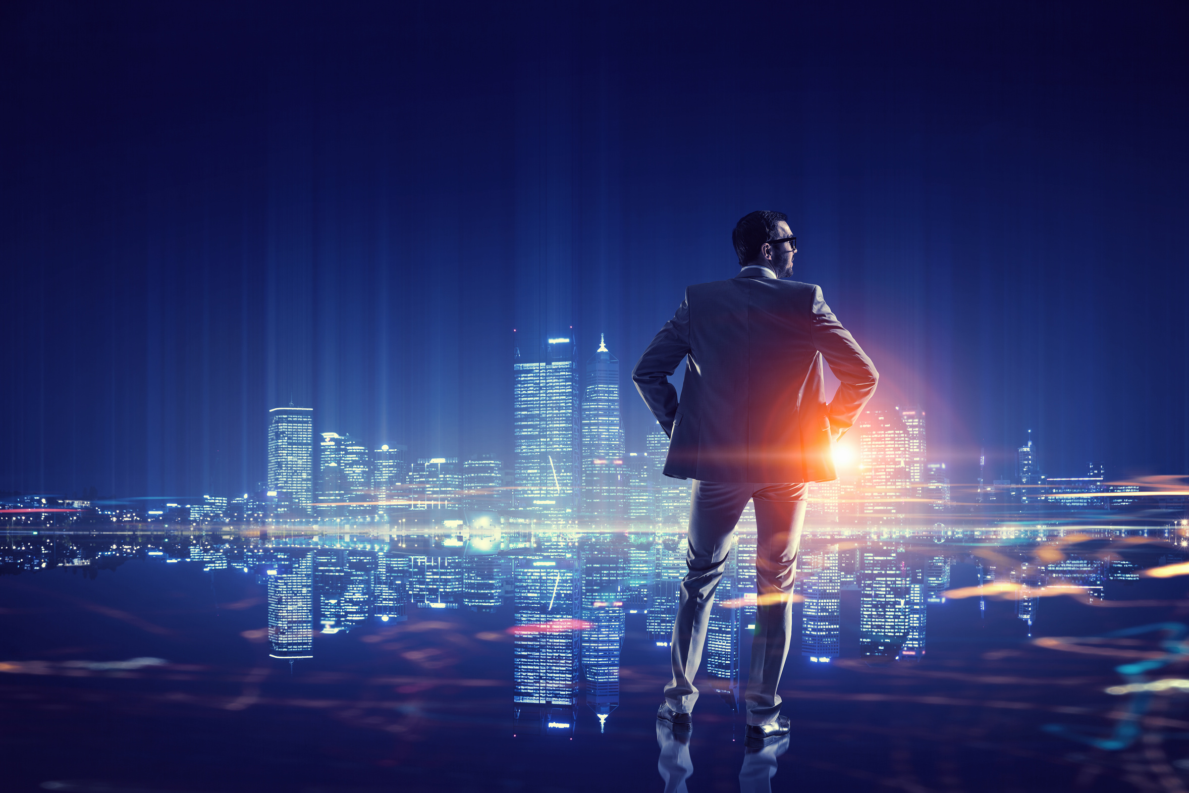 Young elegant businessman against night city background